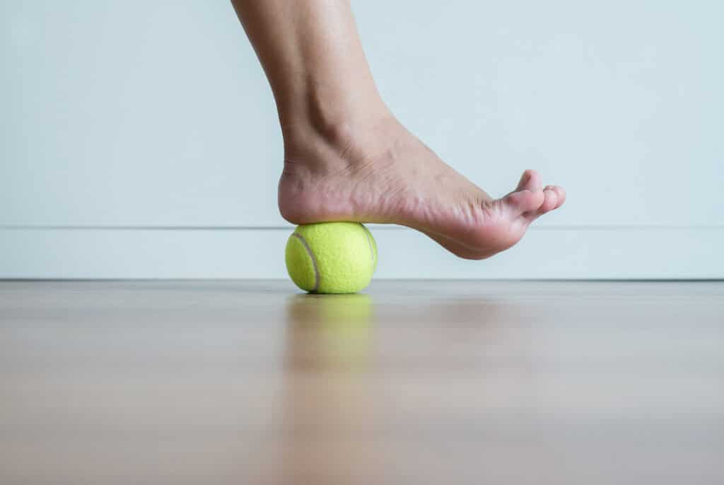 """Traditional """"tennis ball roll"""" stretch for plantar fasciitis."""