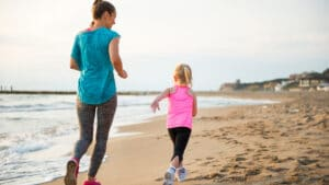 Mom and Daughter Running on Beach